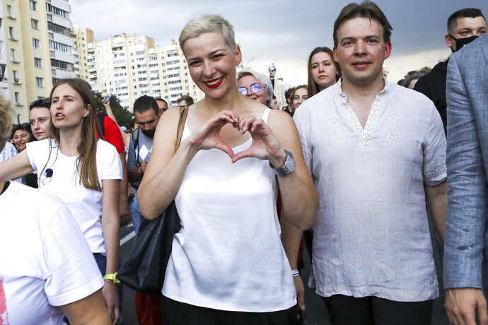 FILE - In this Aug. 30, 2020, file photo, Maria Kolesnikova, one of Belarus' opposition leaders, center, gestures, during a rally in Minsk, Belarus.  Authorities in Belarus detained a lawyer representing a top opposition activist who was jailed this month amid mass protests against the country's authoritarian president, who won a sixth term in a disputed election. The lawyer, Lyudmila Kazak, went missing on Thursday, Sept. 24, 2020 with police confirming later in the day that she had been detained. Kazak was defending Maria Kolesnikova, a key member of a council Belarus' political opposition set up to push for a new presidential election.  (AP Photo/File)