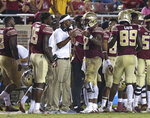 Florida State coach Willie Taggart, center, talks with quarterback Deondre Francois during the fourth quarter of an NCAA college football game against Samford, Saturday, Sept. 8, 2018, in Tallahassee Fla. Florida State won 36-26. (AP Photo/Steve Cannon)