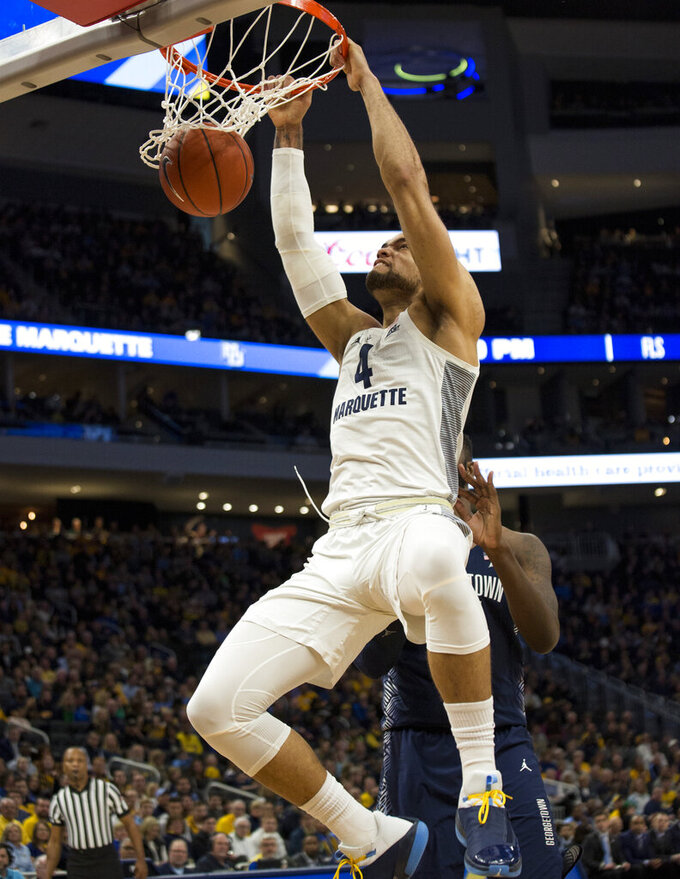 Marquette forward Theo John gets a slam dunk against Georgetown during the first half of an NCAA college basketball game Saturday, March 9, 2019, in Milwaukee. (AP Photo/Darren Hauck)