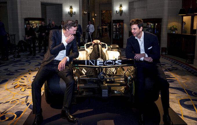 "Toto Wolff, Team Principal & CEO of The Mercedes AMG-PETRONAS F1 Team, right, and INEOS Founder and Chairman Jim Ratcliffe pose for a photo with a Mercedes F1 car and its 2020 livery during a media briefing in London, Monday, Feb. 10, 2020. The Mercedes Formula One team is still waiting to secure a long-term commitment from world champion Lewis Hamilton. Wolff says he hasn't spoken to Hamilton since the Christmas party after agreeing to ""leave each other in peace"" in the offseason. Mercedes has longer certainty from its new sponsor INEOS, the chemicals giant owned by Jim Ratcliffe. (Steven Paston/PA via AP)"