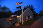 In this Sunday, May 10, 2020, photo a new American flag flies outside the post office on Deer Isle, Maine. The flag was secretly replaced after a plea was posted on the post office bulletin board for help removing the old tattered flag that had been stuck on the pole.