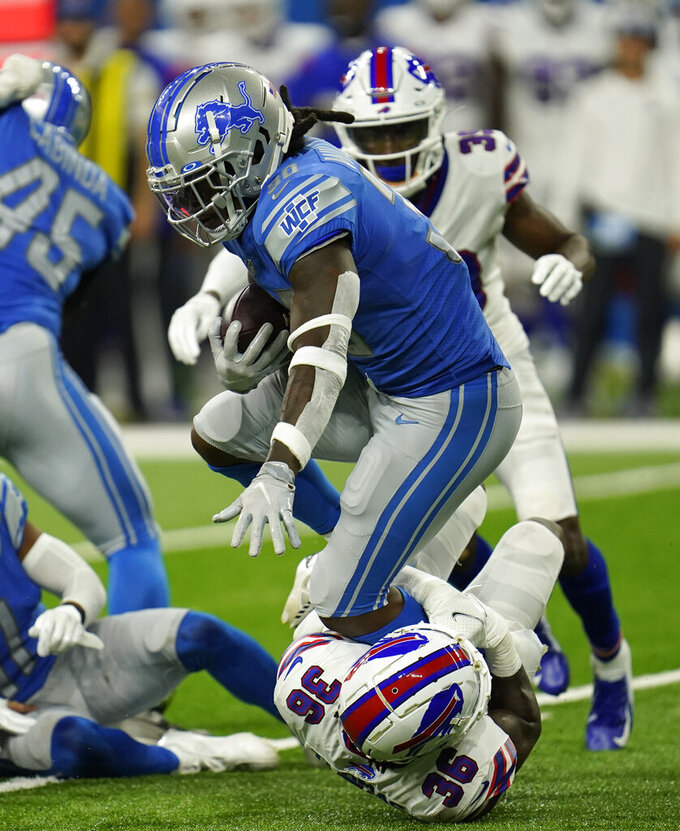 Detroit Lions running back Jamaal Williams (30) is stopped by Buffalo Bills defensive back Josh Thomas (36) during the first half of a preseason NFL football game, Friday, Aug. 13, 2021, in Detroit. (AP Photo/Paul Sancya)