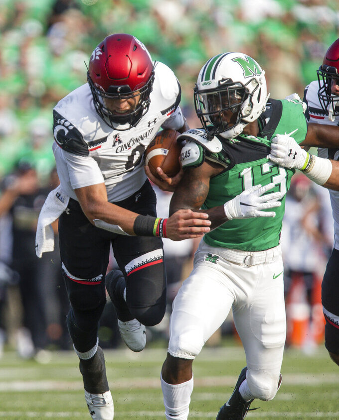 Cincinnati quarterback Desmond Ridder (9) breaks up field on a keeper past Marshall's Nazeeh Johnson (13) an NCAA college football game on Saturday, Sept. 28, 2019, in Huntington, W.Va. (Sholten Singer/The Herald-Dispatch via AP)