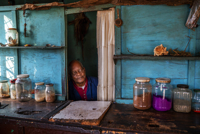 Phoeswa, a South African traditional medicine pharmacist, waits for customers in the densely populated Alexandra township of Johannesburg,  Monday April 6, 2020. More than half of Africa's 54 countries have imposed lockdowns, curfews, travel bans or other restrictions to try to contain the spread of COVID-19. he new coronavirus causes mild or moderate symptoms for most people, but for some, especially older adults and people with existing health problems, it can cause more severe illness or death. (AP Photo/Jerome Delay)