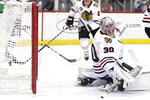 Chicago Blackhawks goaltender Cam Ward looks back as a shot by New Jersey Devils center Kevin Rooney, not visible, enters his net for a goal during the second period of an NHL hockey game, Monday, Jan. 14, 2019, in Newark, N.J. The goal is Rooney's first career goal. (AP Photo/Julio Cortez)