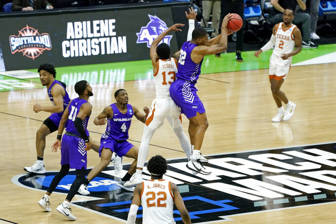 Abilene Christian's Joe Pleasant (32) steals an inbound pass intended for Texas' Jase Febres (13) to end a college basketball game in the first round of the NCAA tournament at Lucas Oil Stadium in Indianapolis Sunday, March 21, 2021. Abilene Christian upset Texas 53-52. (AP Photo/Mark Humphrey)