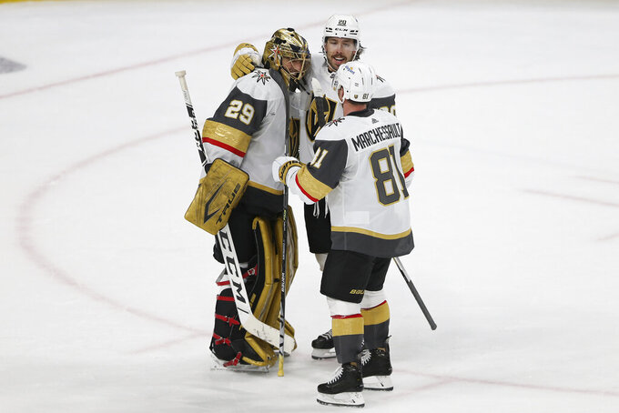 Vegas Golden Knights goalie Marc-Andre Fleury (29) celebrates with Chandler Stephenson (20) and Jonathan Marchessault (81) after the team's 5-2 win over the Minnesota Wild in Game 3 of a first-round NHL hockey playoff series Thursday, May 20, 2021, in St. Paul, Minn. (AP Photo/Stacy Bengs)
