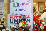 A man sits in front of banners of UMNO (United Malays National Organisation) and PAS (Pan-Malaysian Islamic Party) during an event of officially join alliance in Kuala Lumpur, Malaysia, Saturday, Sept. 14, 2019. Two major opposition parties in Malaysia have forged a political alliance to consolidate support from the country's majority ethnic Malay Muslims, a move that could threaten Prime Minister Mahathir Mohamad's government in the next general elections. (AP Photo/Vincent Thian)