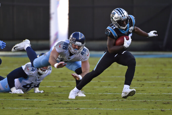 Carolina Panthers wide receiver Greg Dortch (14) runs the ball while Tennessee Titans long snapper Beau Brinkley (48) tries to make the tackle during the second half of an NFL football game in Charlotte, N.C., Sunday, Nov. 3, 2019. (AP Photo/Mike McCarn)