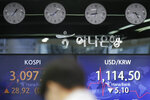 A currency trader walks by the screens showing the Korea Composite Stock Price Index (KOSPI), left, and the foreign exchange rate between U.S. dollar and South Korean won at the foreign exchange dealing room in Seoul, South Korea, Friday, Jan. 29, 2021. Asian stock markets were mixed Friday after Wall Street rebounded from its biggest loss in nearly three months, while Japan reported December factory output weakened. (AP Photo/Lee Jin-man)