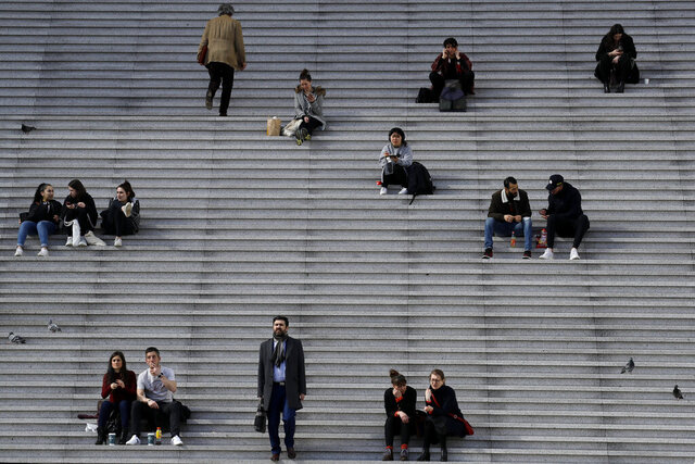 People walk and take a rest at the business district of La Defense outside Paris, Thursday, March 12, 2020. The European Union on Thursday will evaluate President Donald Trump's decision to restrict travel from Europe to the United States amid deep concern over the economic impact of the move with markets already heavily hit by coronavirus. For most people, the new coronavirus causes only mild or moderate symptoms, such as fever and cough. For some, especially older adults and people with existing health problems, it can cause more severe illness, including pneumonia. (AP Photo/Christophe Ena)