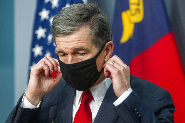 Gov. Roy Cooper removes his mask before answering a reporter's question during a briefing on North Carolina's coronavirus pandemic response at the NC Emergency Operations Center, Wednesday, Sept. 30, 2020, in Raleigh, N.C. (Travis Long/The News & Observer via AP)
