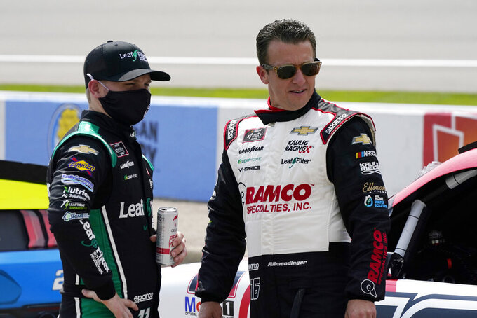 Justin Haley, left, and Justin Haley, A.J. Allmendinger talk before driver introductions at the NASCAR Xfinity Cup Series auto race at Michigan International Speedway, Saturday, Aug. 21, 2021, in Brooklyn, Mich. (AP Photo/Carlos Osorio)