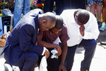 Quincy Mason, center, the son of George Floyd, and family attorney Ben Crump, left, kneel, Wednesday, June 3, 2020 as they visited the site of a memorial in Minneapolis where Floyd was arrested on May 25  and died while in police custody. Video shared online by a bystander showed a white officer kneeling on his neck during his arrest as he pleaded that he couldn't breathe. (AP Photo/Jim Mone)