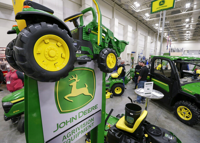 FILE - In this Feb. 23, 2018 file photo, John Deere products, including a toy tractor on the sign, are on display at a home and garden trade show in Council Bluffs, Iowa. John Deere reports financial earnings Friday, Aug. 16, 2019. (AP Photo/Nati Harnik, File)