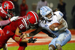 North Carolina's Michael Carter (8) bounces off the tackle of North Carolina State's C.J. Hart (15) during the first half of an NCAA college football game in Raleigh, N.C., Saturday, Nov. 30, 2019. (AP Photo/Karl B DeBlaker)