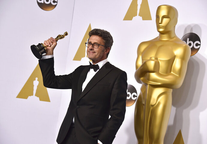 FILE - In this Sunday, Feb. 22, 2015 file photo, Pawel Pawlikowski poses in the press room with the award for best foreign language film for