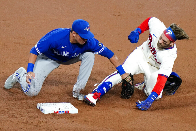Philadelphia Phillies' Bryce Harper, right, is tagged out at second by Toronto Blue Jays second baseman Joe Panik after trying to stretch a single during the first inning of the second baseball game in a doubleheader, Friday, Sept. 18, 2020, in Philadelphia. (AP Photo/Matt Slocum)