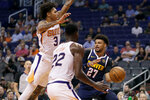 Denver Nuggets guard Jamal Murray (27) dishes around Phoenix Suns forward Kelly Oubre Jr. (3) and center Deandre Ayton (22) during the first half of an NBA preseason basketball game, Monday, Oct. 14, 2019, in Phoenix. (AP Photo/Matt York)