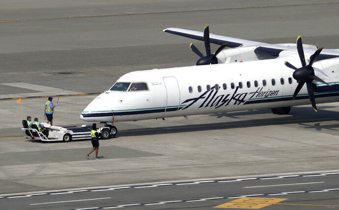 File - In this Aug. 13, 2018 file photo, a Horizon Air Q400 turboprop airplane, part of Alaska Air Group, is moved into position by airport workers at Seattle-Tacoma International Airport in SeaTac, Wash. The plane is the same model of aircraft stolen from the airport by an airline ground agent which later crashed into crashed into a small island in the Puget Sound, killing the man. Authorities say the Seattle airport ground crew worker who stole an empty commercial airplane had apparently searched online for flight instruction videos before he took off on a dizzying ride that soon crashed into a small island. The FBI announced Friday, Nov. 9, 2018, that it's concluding the investigation into the August 10 incident after determining that Richard Russell, 28, of Sumner, Washington, acted alone from Seattle-Tacoma International Airport. (AP Photo/Elaine Thompson, File)