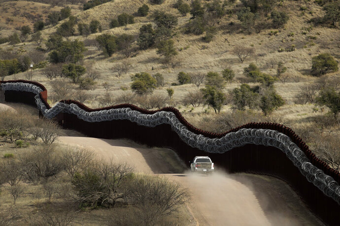 FILE - This March 2, 2019, file photo, shows a Customs and Border Control agent patrolling on the US side of a razor-wire-covered border wall along the Mexico east of Nogales, Ariz. Federal prosecutors are getting ready to announce whether they'll retry a border activist after a U.S. jury was unable to reach a verdict against him on charges of conspiracy to transport and harbor migrants. (AP Photo/Charlie Riedel, File)
