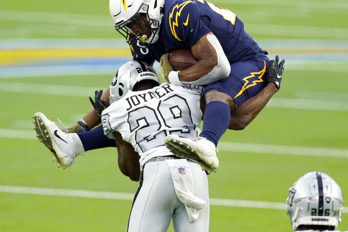 Los Angeles Chargers running back Joshua Kelley, above, tries to leap over Las Vegas Raiders free safety Lamarcus Joyner during the second half of an NFL football game Sunday, Nov. 8, 2020, in Inglewood, Calif. (AP Photo/Ashley Landis)