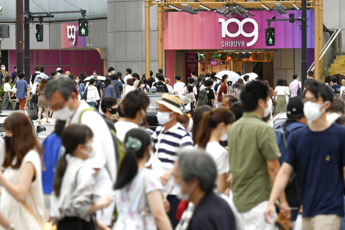 """FILE - In this Aug. 7, 2021, file photo, people wearing face masks make their way at an intersection in Tokyo Saturday, Aug. 7, 2021. When the Tokyo Olympics began during a worsening pandemic, the majority of the host nation was in opposition, with Emperor Naruhito dropping the word """"celebrating"""" from his opening declaration of welcome. But once the Games got underway and local media switched to covering Japanese athletes' """"medal rush,"""" many were won over.  (Kyodo News via AP, File)"""