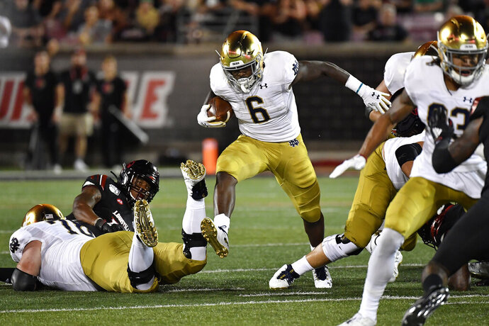 Notre Dame running back Tony Jones Jr. (6) runs through an opening in the Louisville defensive line during the first half of an NCAA college football game against Louisville in Louisville, Ky., Monday, Sept. 2, 2019. (AP Photo/Timothy D. Easley)