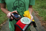 Arden Blumenthal, a NY-NJ Trails conference intern, removes a GPS from Dia's dog pack in Harriman State Park in Tuxedo, N.Y., Tuesday, Aug. 6, 2019. The nonprofit New York-New Jersey Trail Conference has trained Dia, a Labrador retriever, to find Scotch broom plants in two state parks 50 miles (80 kilometers) north of New York City. The invasive shrub is widespread in the Pacific Northwest but new to New York, and land managers hope to eradicate it before it gets established.  (AP Photo/Seth Wenig)