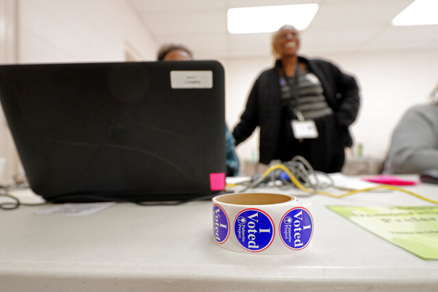 A roll of voting stickers sits on a table as people arrive to vote in the Democratic primary in Hopkins, S.C., Saturday, Feb. 29, 2020. (AP Photo/Gerald Herbert)