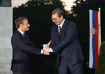 French President Emmanuel Macron, left, and Serbian President Aleksandar Vucic shake hands during an event at Veliki Kalemegdan Park in Belgrade, Serbia, Monday, July 15, 2019. French President Emmanuel Macron is for a two days official visit in Belgrade. (AP Photo/Darko Vojinovic)