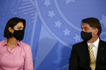 Brazil's President Jair Bolsonaro talks with his wife, first lady Michelle Bolsonaro, both wearing masks amid the COVID-19 pandemic, during an event promoting a government campaign against domestic violence at Planalto presidential palace in Brasilia, Brazil, Friday, May 15, 2020. (AP Photo/Eraldo Peres)