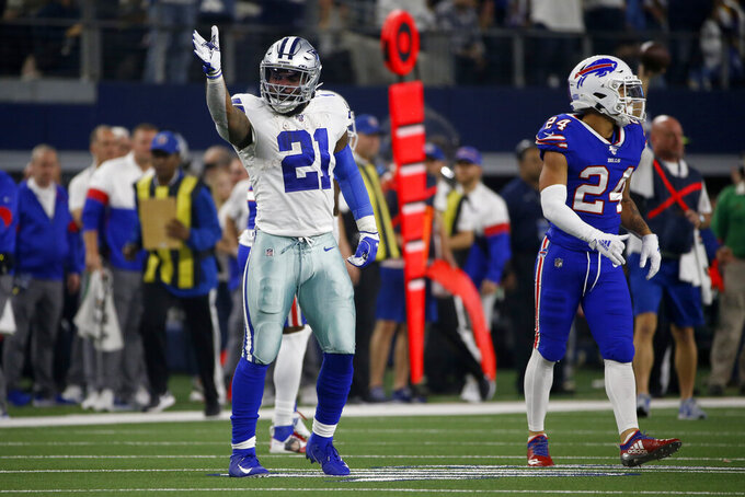 Dallas Cowboys running back Ezekiel Elliott (21) signals first down after running the ball as Buffalo Bills cornerback Taron Johnson (24) looks on in the first half of an NFL football game in Arlington, Texas, Thursday, Nov. 28, 2019. (AP Photo/Ron Jenkins)