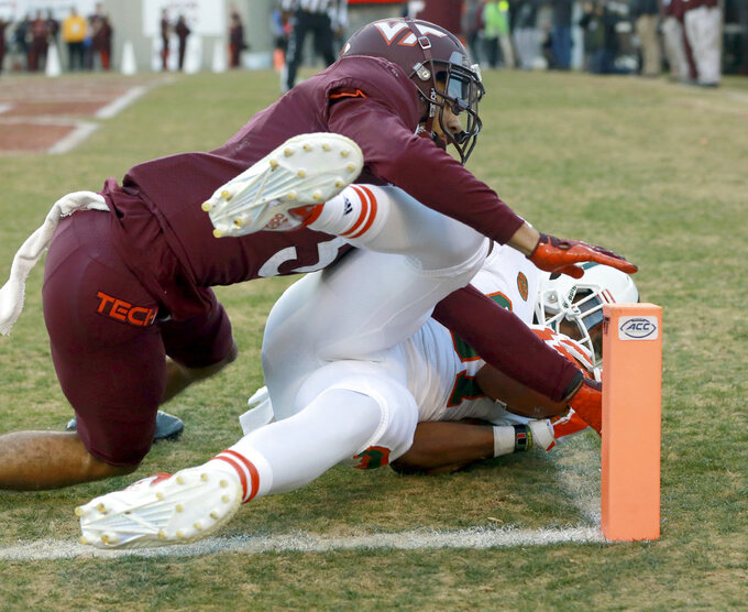Miami's Darrell Langham (81) controls a touchdown pass from quarterback N'Kosi Perry (5) as Virginia Tech defender Ryan Willis (5) falls on top of him in the first half of an NCAA college football game in Blacksburg, Va., Saturday, Nov. 17 2018. (Matt Gentry/The Roanoke Times via AP)