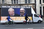 Cyclists pass a mobile anti-Brexit billboard at Trafalgar square in London, Tuesday, Dec. 10, 2019. Britain goes to the polls on Thursday, Dec. 12. (AP Photo/Srdjan Nedeljkovic)