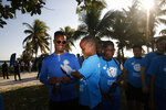Super Bowl host committee member Rashad Thomas and his son Rasheem, 6, clean the beach at the Historic Virginia Key Beach Park for the Huddle for 100 beach clean up on Tuesday, Jan. 28, 2020, in Miami. Climate change poses a threat to South Florida's way of life, including Miami's customary spot in the NFL's Super Bowl rotation. The game will be played Sunday in Miami for the 11th time, the most of any city. But the sea and temperature are rising, which could eventually make South Florida an unsuitable Super Bowl site.  (AP Photo/Brynn Anderson)