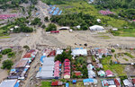 This aerial shot taken on Sunday, March 17, 2019 shows the area affected by flash floods in Sentani, Papua province, Indonesia. Flash floods and mudslides triggered by downpours tore through mountainside villages in Indonesia's easternmost province, killing dozens of people, disaster officials said. (AP Photo/Barce Rumkabu)