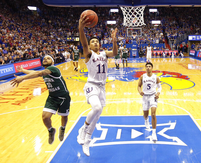 Kansas' Devon Dotson (11) gets past Eastern Michigan's Malik Ellison (10) to put up a shot during the first half of an NCAA college basketball game Saturday, Dec. 29, 2018, in Lawrence, Kan. (AP Photo/Charlie Riedel)