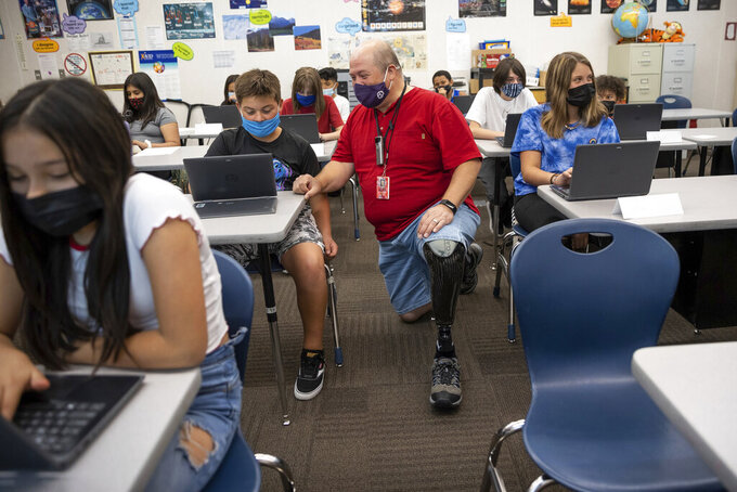 Bill Coleman, a sixth grade teacher, chats with Jerry Oyler during class at Nibley Park School in Salt Lake City on Tuesday, Aug. 24, 2021.  Salt Lake City school officials say that almost everyone is complying with a classroom mask mandate without police enforcement. (Spenser Heaps/The Deseret News via AP)