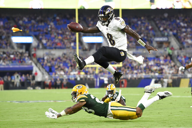 FILE - In this Aug. 15, 2019, file photo, Baltimore Ravens quarterback Lamar Jackson (8) leaps over Green Bay Packers cornerback Jaire Alexander (23) during the first half of a NFL football preseason game, in Baltimore. Ravens offensive coordinator Greg Roman is tweaking and refining a record-setting unit led by NFL MVP Lamar Jackson, who is expected to again be the key component of an attack with several newcomers in the mix.  (AP Photo/Gail Burton, File)