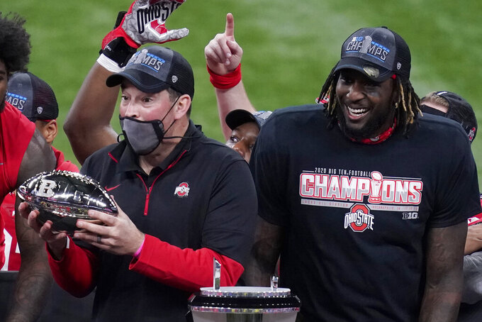 Ohio State head coach Ryan Day, left, holds the trophy along side running back Trey Sermon after defeating Northwestern in the Big Ten championship NCAA college football game, Saturday, Dec. 19, 2020, in Indianapolis. Ohio State won 22-10. (AP Photo/Darron Cummings)
