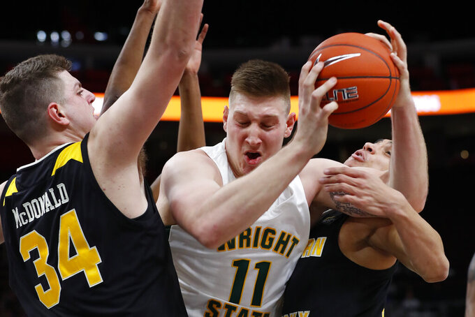 Wright State center Loudon Love (11) tries to drive between Northern Kentucky forward Drew McDonald (34) and Northern Kentucky guard Paul Djoko (2) in the first half of an NCAA college men's basketball game in the Horizon League conference tournament championship in Detroit, Tuesday, March 12, 2019. (AP Photo/Paul Sancya)