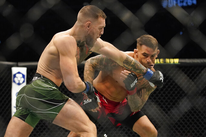 Conor McGregor, left, punches Dustin Poirier during a UFC 264 lightweight mixed martial arts bout Saturday, July 10, 2021, in Las Vegas. (AP Photo/John Locher)