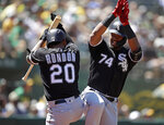 Chicago White Sox Eloy Jimenez, right, celebrates with Jose Rondon, left, after hitting a homerun off Oakland Athletics' Brett Anderson in the seventh inning of a baseball game Sunday, July 14, 2019, in Oakland, Calif. (AP Photo/Ben Margot)