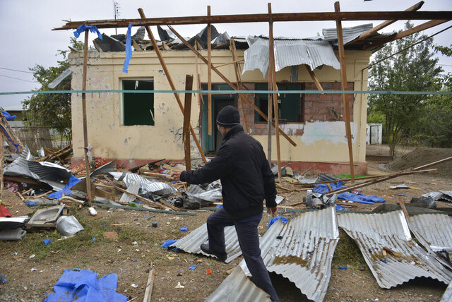 A man walks past a house destroyed by shelling during fighting over the breakaway region of Nagorno-Karabakh in Agdam, Azerbaijan, Thursday, Oct. 1, 2020. Clashes broke out Sunday in Nagorno-Karabakh, a region within Azerbaijan that has been controlled by ethnic Armenian forces backed by the Armenian government since the end of a separatist war a quarter-century ago. Fighting has continued unchecked since then, killing dozens and leaving scores wounded. Armenian and Azerbaijani forces blame each other for continuing attacks. (AP Photo/Aziz Karimov)