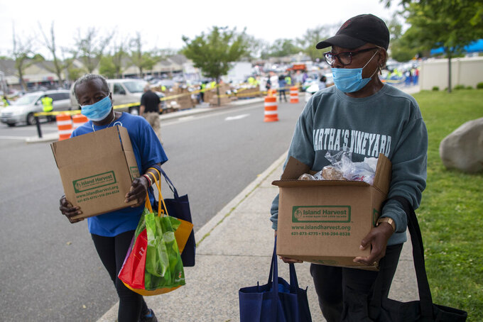 In this Thursday, May 28, 2020, photo, Betty Chandler, left, and Sheila Barron carry groceries they received during a food distribution drive sponsored by Island Harvest Food Bank in Valley Stream, N.Y.  The Valley Stream stream donations were just one of many events Island Harvest has conducted throughout the area recently. (AP Photo/Mary Altaffer)