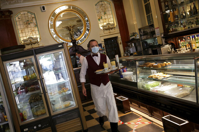 A waiter wearing a face mask carries a tray at the Versailles restaurant and pastry shop in Lisbon, Monday, May 18, 2020. Some cafes and restaurants are reopening in Portugal on Monday. The government is gradually easing measures introduced to stem the spread of the new coronavirus. (AP Photo/Armando Franca)