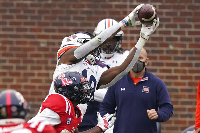 Auburn wide receiver Seth Williams, right, stretches beyond Mississippi defensive back Keidron Smith, left, to catch what becomes a 42-yard touchdown pass during the second half of an NCAA college football game in Oxford, Miss., Saturday, Oct. 24, 2020.  (AP Photo/Rogelio V. Solis)