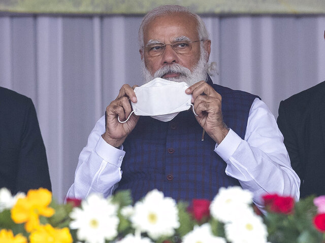 Indian Prime Minister Narendra Modi holds a face mask as he attends a a rally in Sivsagar, east of Gauhati, India, Saturday, Jan. 23, 2021. Modi attended a rally to distribute land allotment certificates to landless indigenous people in Assam's Sivasagar district, under a special programme of the state government. (AP Photo/Anupam Nath)