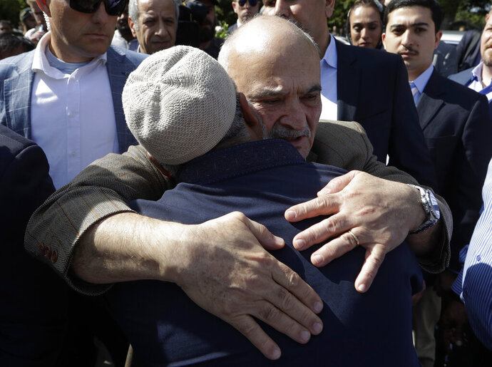 His Royal Highness Prince El Hassan bin Talal Hashemite, of the Kingdom of Jordan, embraces a worshipper outside the Al Noor mosque in Christchurch, New Zealand, Saturday, March 23, 2019. The mosque reopened today following the March 15 mass shooting. (AP Photo/Mark Baker)